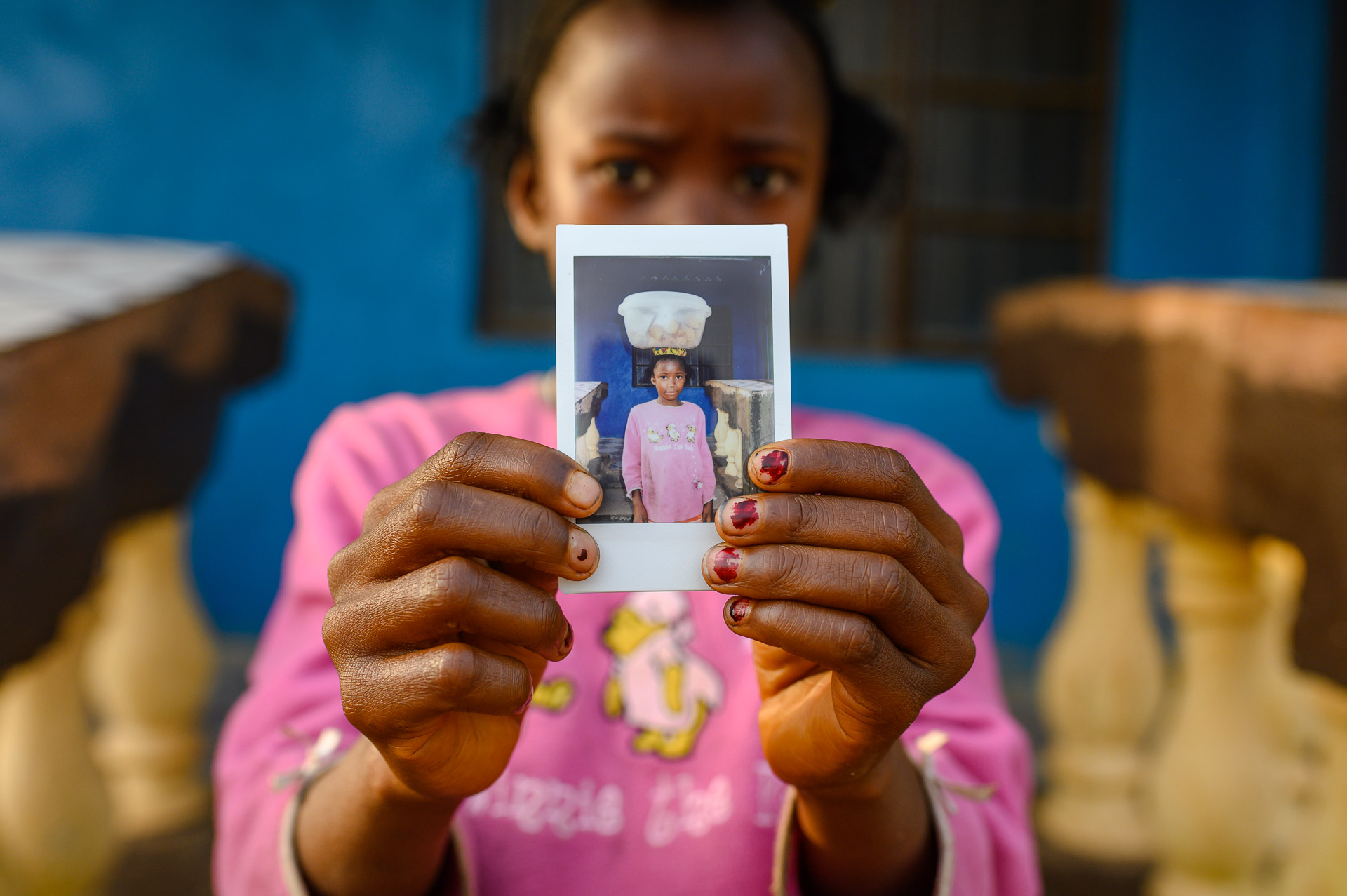 Little girl holding polariod, slowfood international,sierra leone street photography